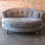 Large Round Chaise Lounge With Tufted Back And Wooden Leg With Wheel Placed On C...