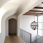 Mediterranean home features an iron staircase railing illuminated by a wood sphe...